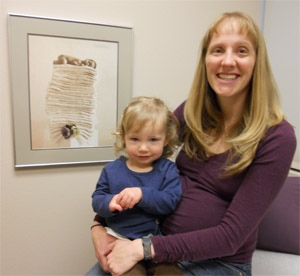 Photo of Pregnant mother with yound daughter sitting in her lap at Women's Healthwise in Longmont, CO