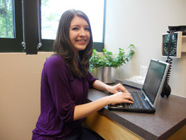 Photo of Kayla Estes sitting at computer at Women's Healthwise
